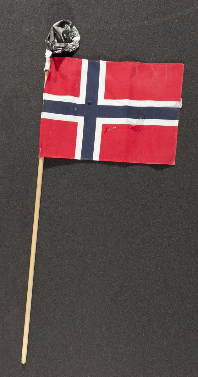 """Flagg innsamlet etter terrorhandlingen 22. juli 2011 fra minnesmarkeringene i Lillestrøm.   Klassisk norsk flagg slik vi kjenner det fra 17.mai feiringer: Blått kors i midten, hvitt kors som """"omkranser"""" det blå (litt tynnere fargefelt) på en rød bakgrunn, de blå og hvite korset går helt til kanten av flagget. Dimensjonene på feltene er slik at de to røde felten mot pinnen er halvparten så store som de to ytterste røde feltene. Flagget brukes både av barn og voksne. På toppen av flaggpinnen er det festet en stålgrå ballong. Den er festet med hvit tape. Ballongen har mistet all luft og ser ut som den har vært i kontakt med varme/ild, da den delevis er tørket og sprø. Det er også sølt stearin flere steder på flagget."""