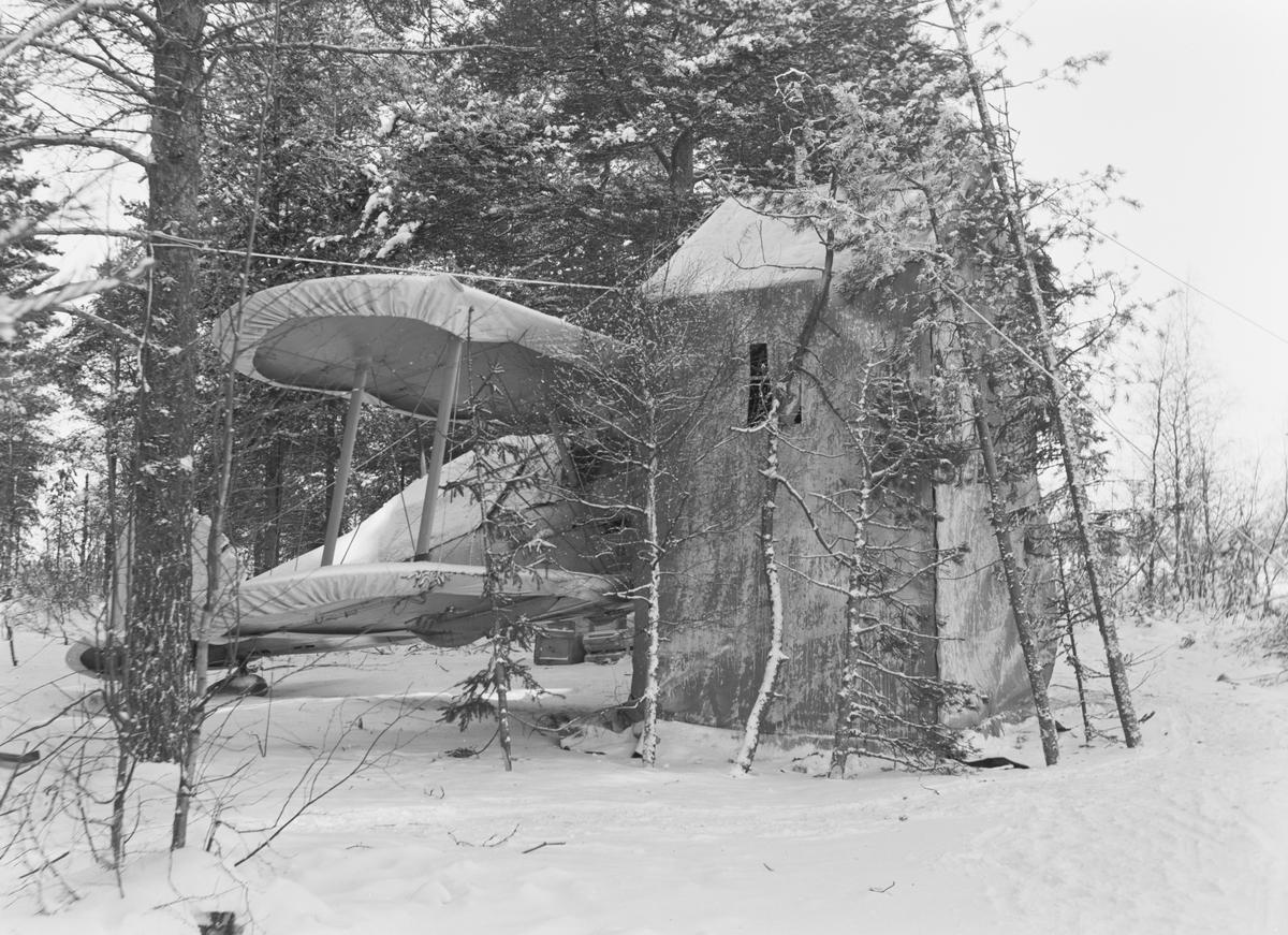 """Flygplan i flygplanvärn vid Svenska frivilligkåren i Finland, F 19. Vy från sidan, flygplanet placerat i skyddshus """"Modell Englund"""""""