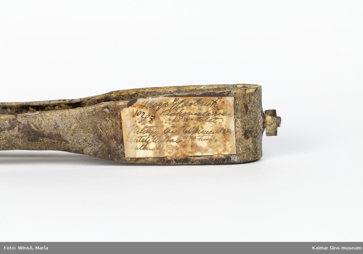 KLM 10207. Sax, flasksax. Användes vid glasblåsning, för formande av buteljhalsar. Av metall med två ben som nedtill är gängade och försedda med hål. I mitten en fastskruvad metallstång som längst ut ser ut att vara försedd med en stämpel. Två trissor som suttit på benen saknas.