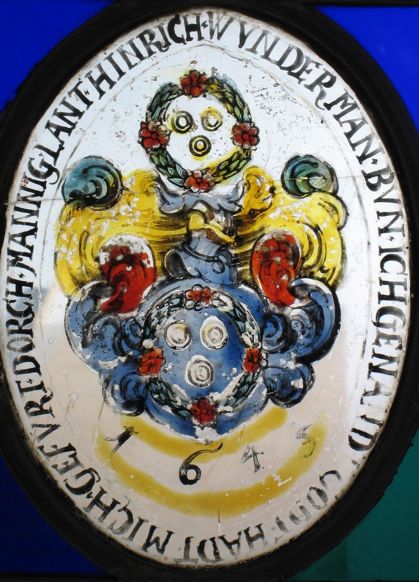 2  blomsterkranser, hver med to ringer, mellom disse  bølgende former i blått, rødt og oker, årstallet  1645.  Tekst rundt bildemotivet.