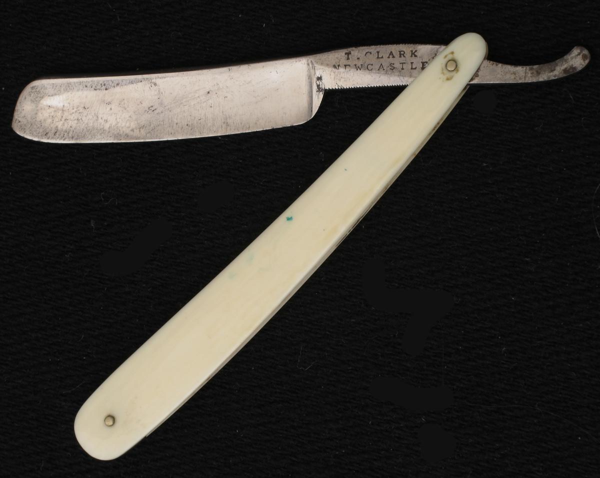 Barberkniv i futteral.  Stållblad st.: T. Clark Newcastle, benskaft.   Sort pappfutteral med firmanavn. trukket med lær.