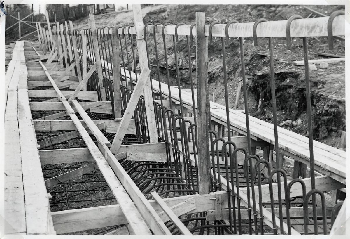 Uppförande av stödmur för järnvägsbanken vid byggnationen av ny järnvägsviadukt över Norrtullsgatan. Belägen ca 100 m öster om östra landfästet i nya vidaukten. Grundplattan armerad.
