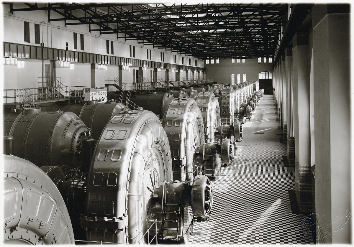 Interiörbild av turbiner i maskinsalen. Trollhättans kraftstation kallas även Olidans kraftverk. Olidestationen är den äldsta bland de av staten byggda och ägda vattenkraftsanläggningarna. 1906-års riksdag tog utbyggnadsbeslutet, och arbetet startade samma år. Stationen uppfördes i 3 steg, varav de 4 första togs i drift 1910. Ytterligare 4 aggregat ingick i den andra utbyggnadsetappen som gjordes 1912-1914. Den tredje etappen om 5 aggregat slutfördes 1918-1921.