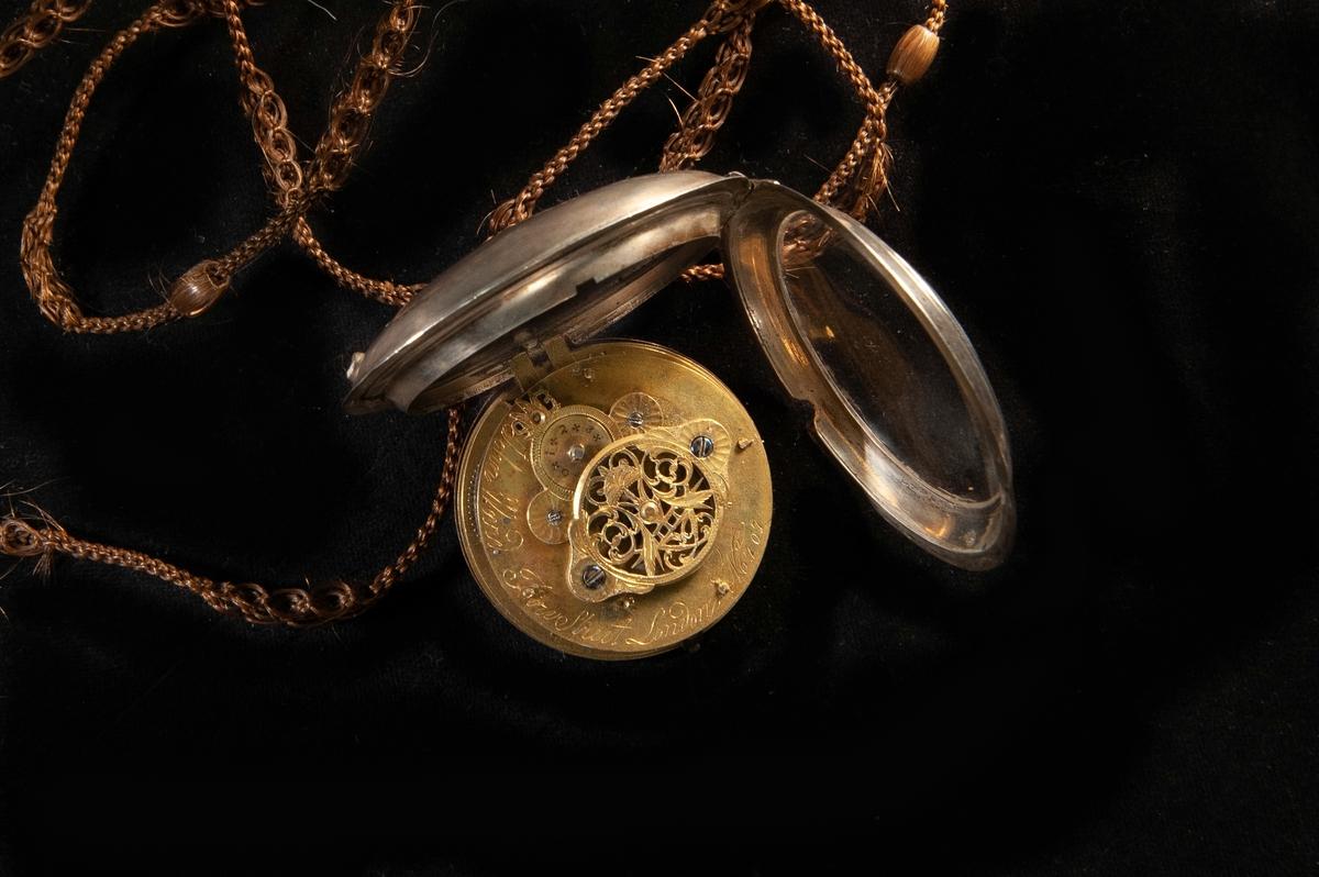 Ett spindelur med fast boett. Urtavla med arabiska siffror.  Boett av silver med engelska stämplar. Graverad text på urverket och graverade initialer på baksidan. Till uret hör en klockkedja av flätat hårarbete (längd 1200 mm).