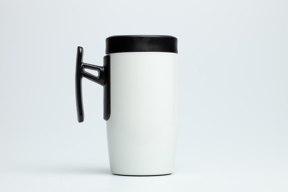 En hvit Statoilkopp med sort hank. Koppen er i grå metall på innsiden. Statoillogo i oransje på koppen. På en etikett på koppen er en Statoillogo,