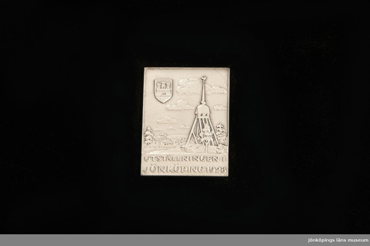 """Rektangulär utställningsplakett av silver, förvarad i ask. Utdelad vid  utställningen i Jönköping 1928. Plackettens baksida är stämplad. Asken är i brun papp. Lockets insida är fodrat med gräddvitt siden, tryckt med """"C.C. Sporrong & Co. Stockholm"""" i guld. Askens botten är fodrad med gräddvitt sammet."""