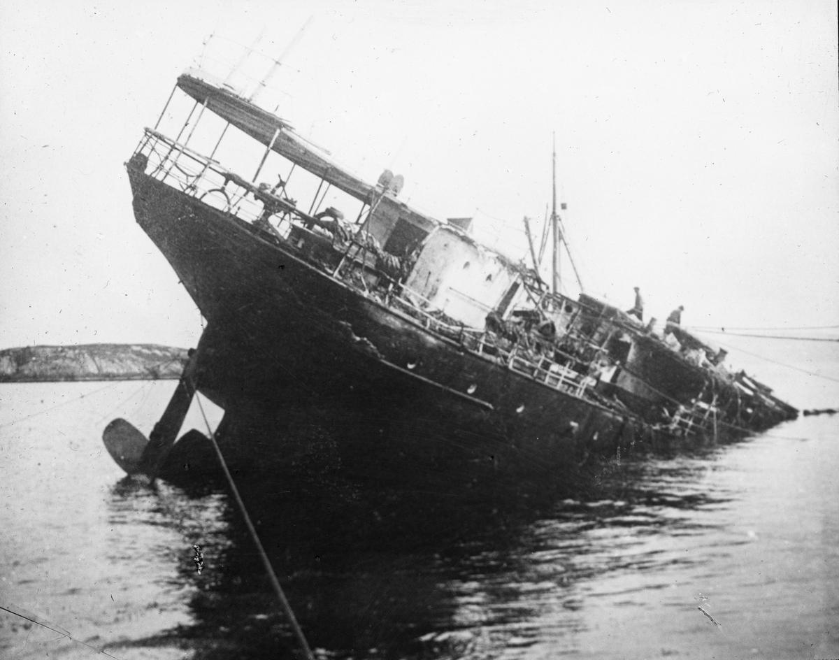 Akterenden på en fjordabåt, resten av fartøyet ligger under vann.