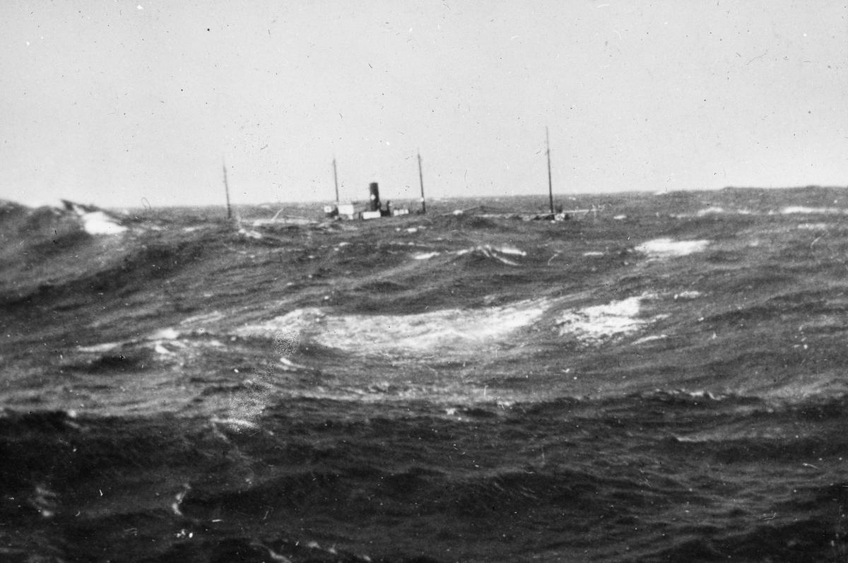 Havarert dampskip, bølger slår over fartøyet.