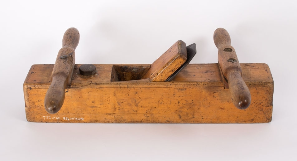 Okshøvel. Rektangulær høvel med dreide håndtak foran og bak. Skåret kile og smidd regulerbart høveljern.
