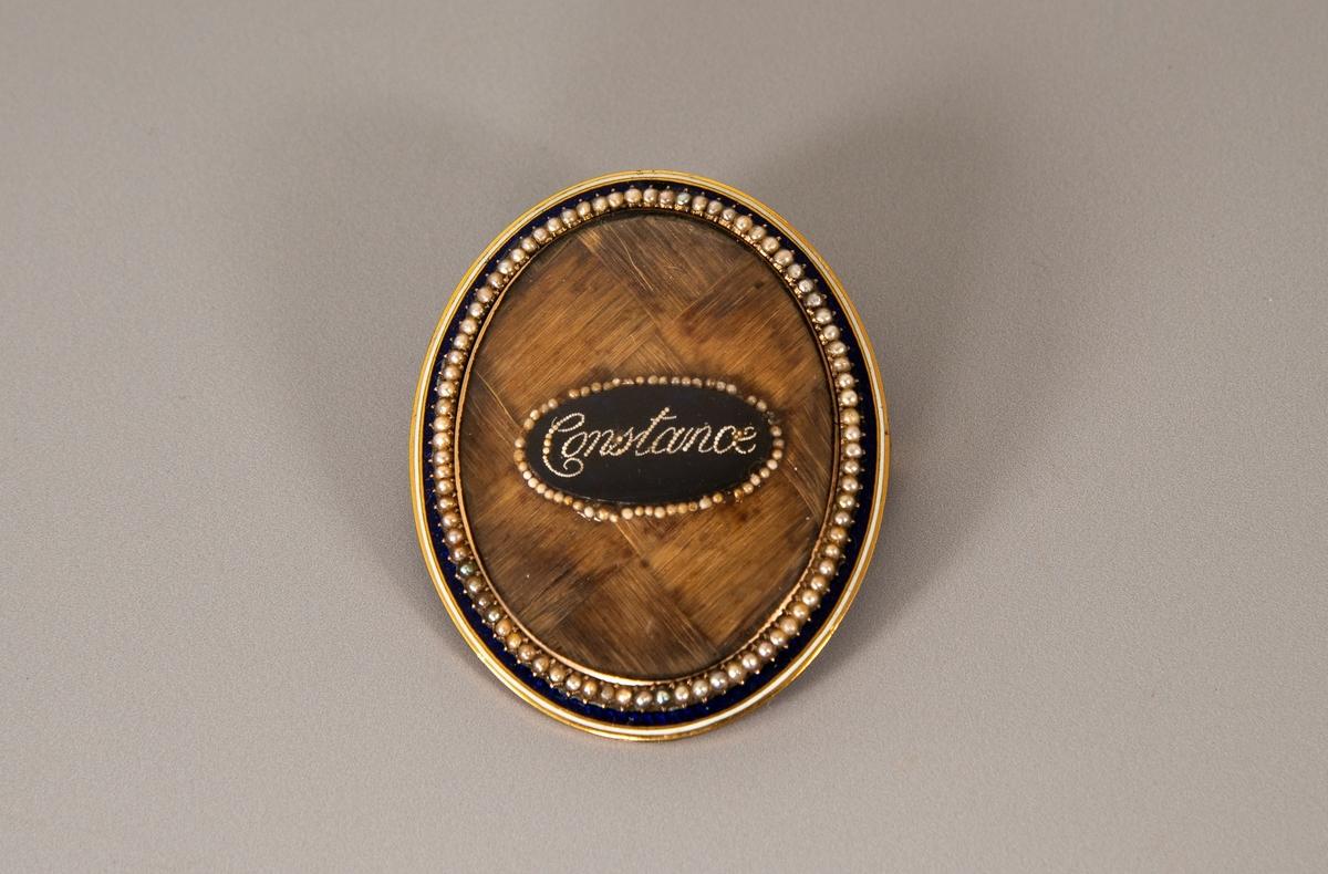 """Oval brosje med nål på baksiden. Navnet """"Constance"""" er stavet med små perler på dypblå emalje, som er omgitt av flettet hår. Mest sannsynlig er håret fra Constance selv."""