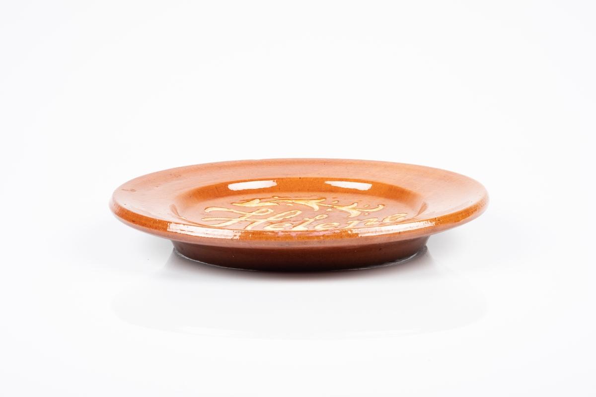 Rund keramikkfat med inskripsjon. Fatet er glasert med brun glasur og inskripsjonen er i gult glasur.