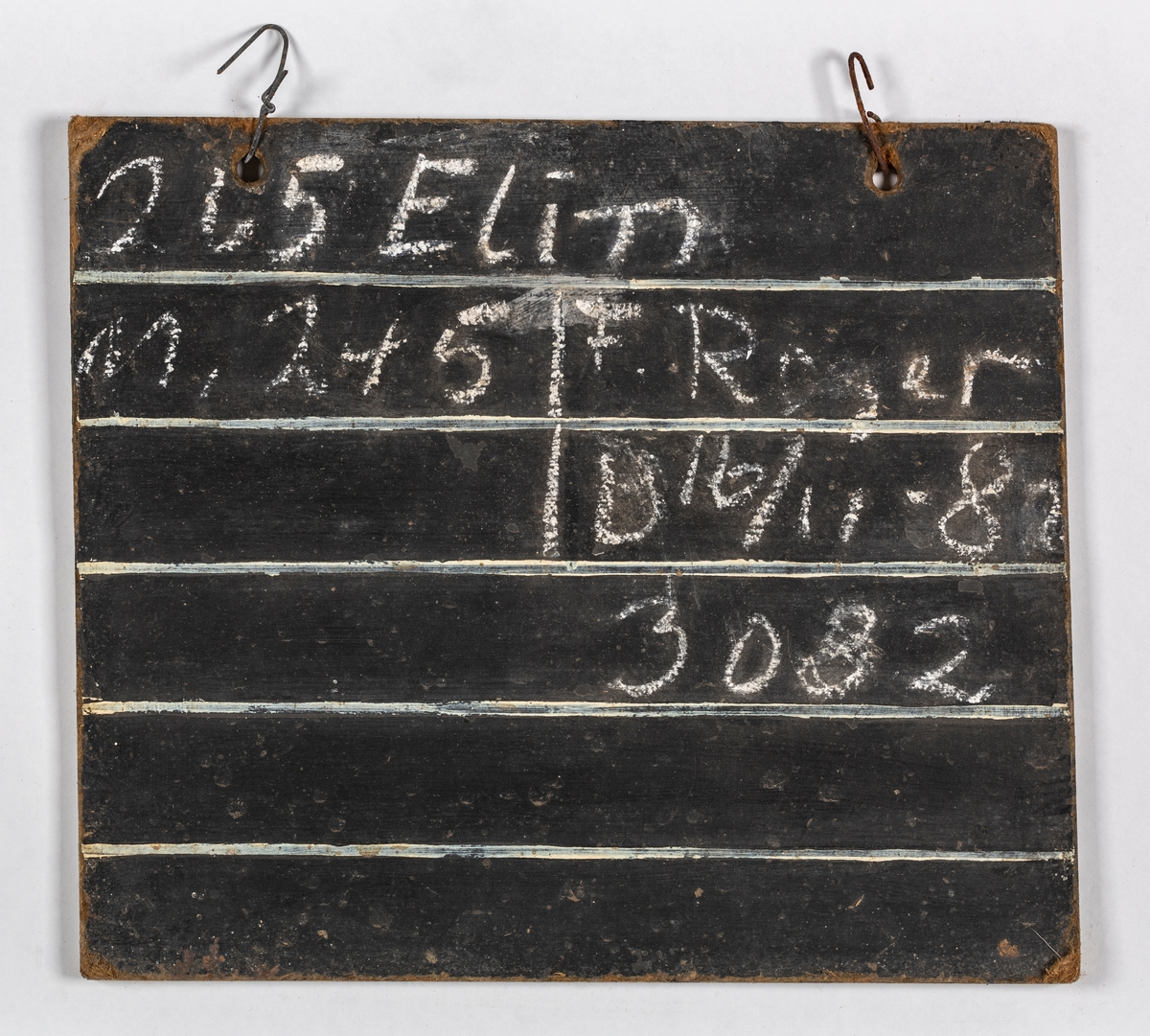 Skiltet er ferdig inndelt i felt. Det påføres nummer, navn og fødselsdato på ku,  far og mor og datoer for kalving og bedekking. Skiltet  er et rektangulært stykke huntonitt, malt med svart på begge siden. Bokstaver, linjer og ruter er påført med hvit strek. Det har blitt skrevet med kritt, som er lett å ta vekk. Skiltet har to hull i øvre langside med metallkrampe på, til oppheng i fjøset.