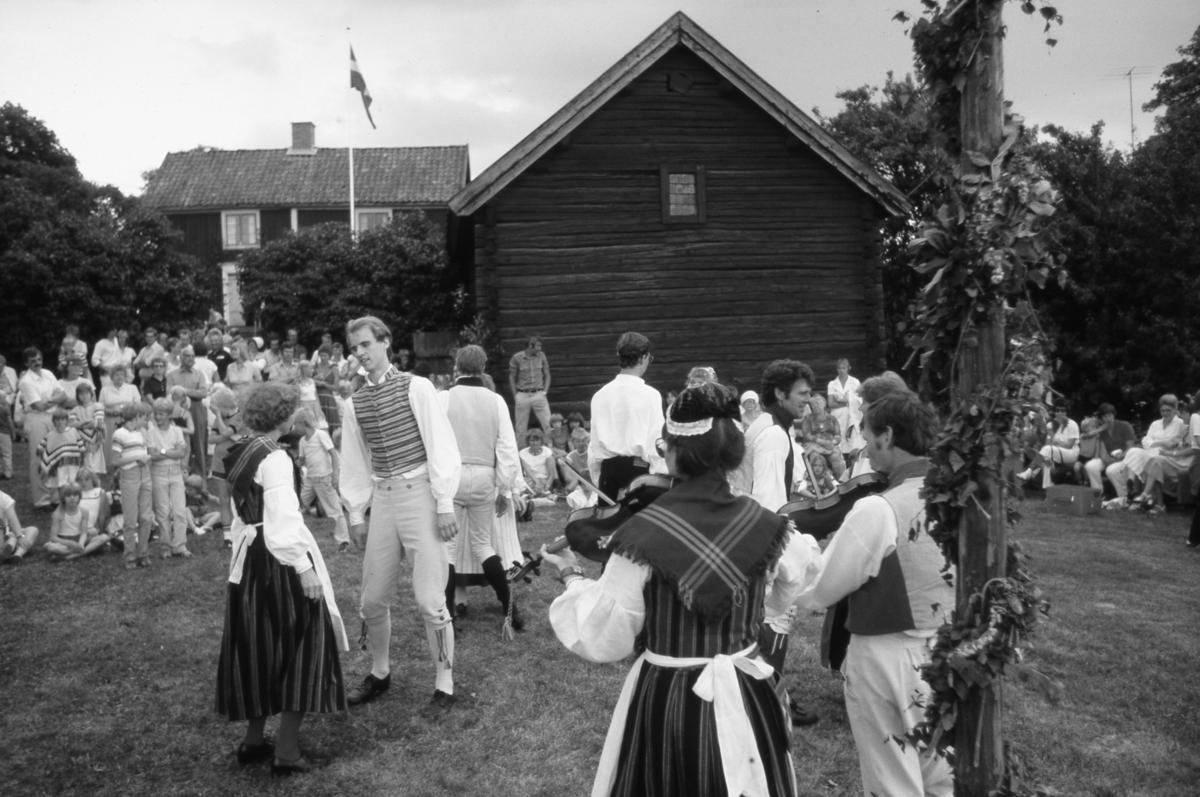 Arboga Folkdansgille har uppvisning på Abramsgården i Medåker. Det är midsommar och mycket publik. Samtliga dansare och spelmän bär folkdräkt. Till vänster dansar Gudrun Trygg och Bengt Frid. Med ryggen mot fotografen ses Stefan Törnqvist. Mellan fiolspelarna ses Karl-Barthold Widlund. Fiolspelarna, vid midsommarstången, är Berit Westin och Johan Geben. Gudrun Trygg och Berit Westin bär Västerfärnebodräkten, den vanligast förekommande kvinnliga folkdräkten i Västmanland.