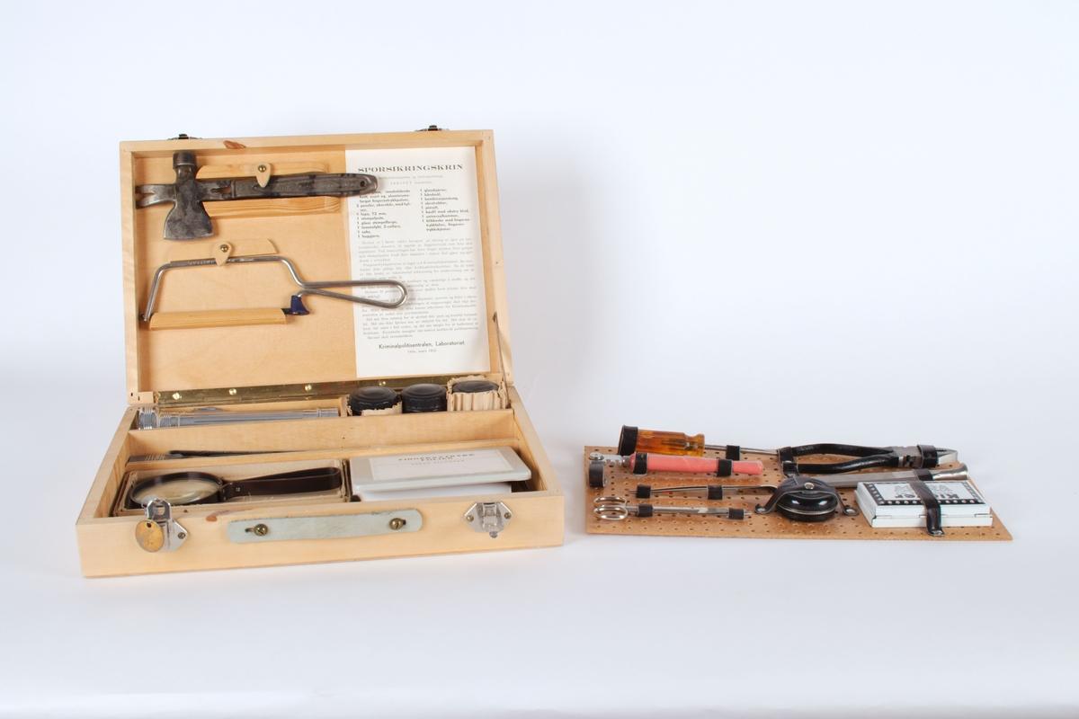 Komplett sporsikringsskrin i tre. Skrinet inneholder redskaper til bruk under sikring og innsamling av bevis; fil, hammer, pinsett, glasskjærerr, båndmål, tang, skrutrekker, saks, lupe og utstyr for å sikre fingeravtrykk.