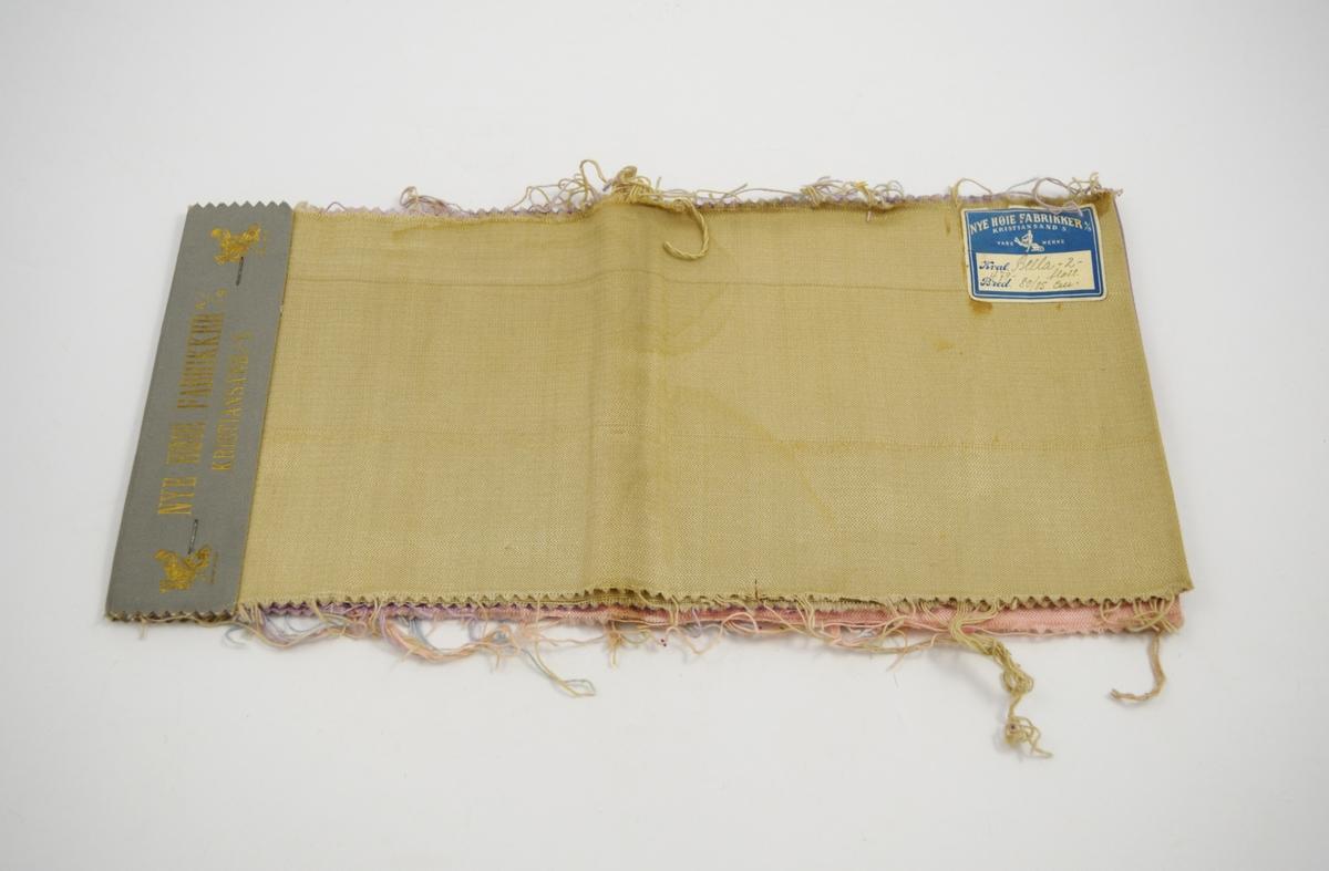 "Rektangulære, lange tekstilprøver brettet dobbelt og stiftet sammen med et papiromslag. Hver stoffprøve er merket med en klistrelapp med nummer. Heftet viser kvalitet ""Bella-2-floss"" og design 479, 478, 423, 477."