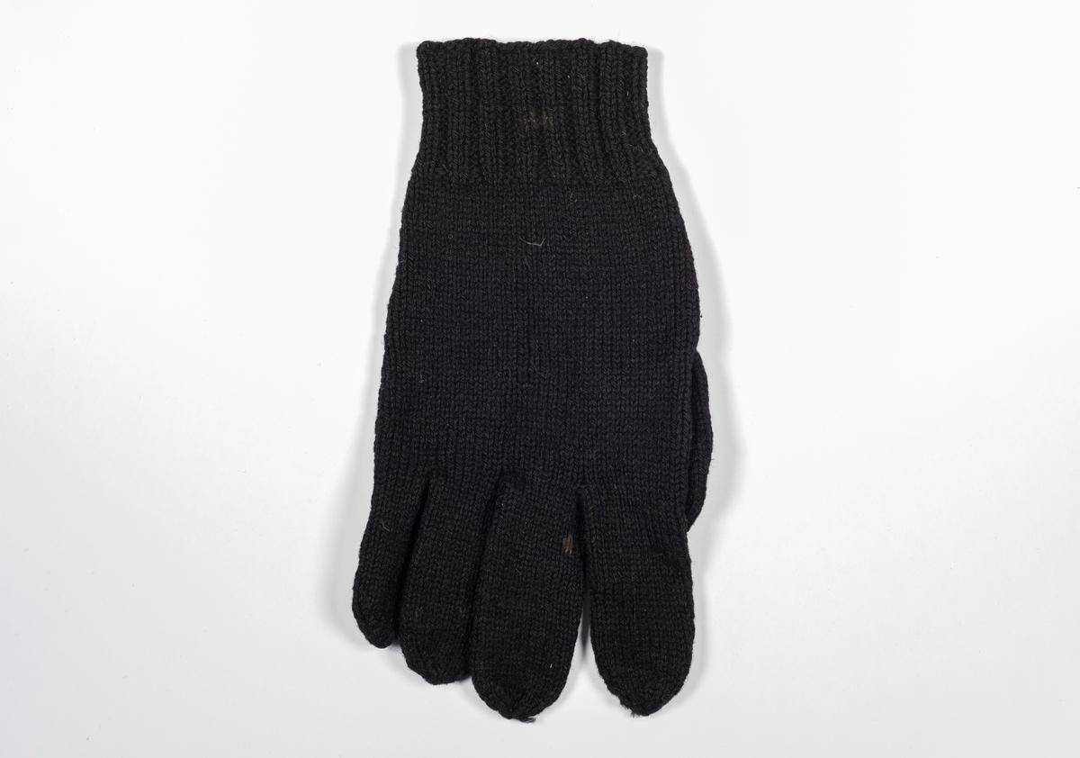 En svart strikket hanske med broderte initialer.