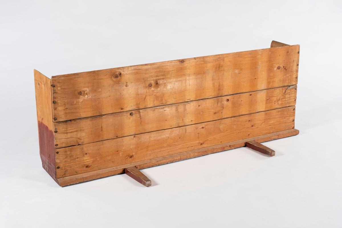 Uttrekkbar del av seng med to ben og profilert sengevang på lansiden. Sengebunnen består av tre planker.