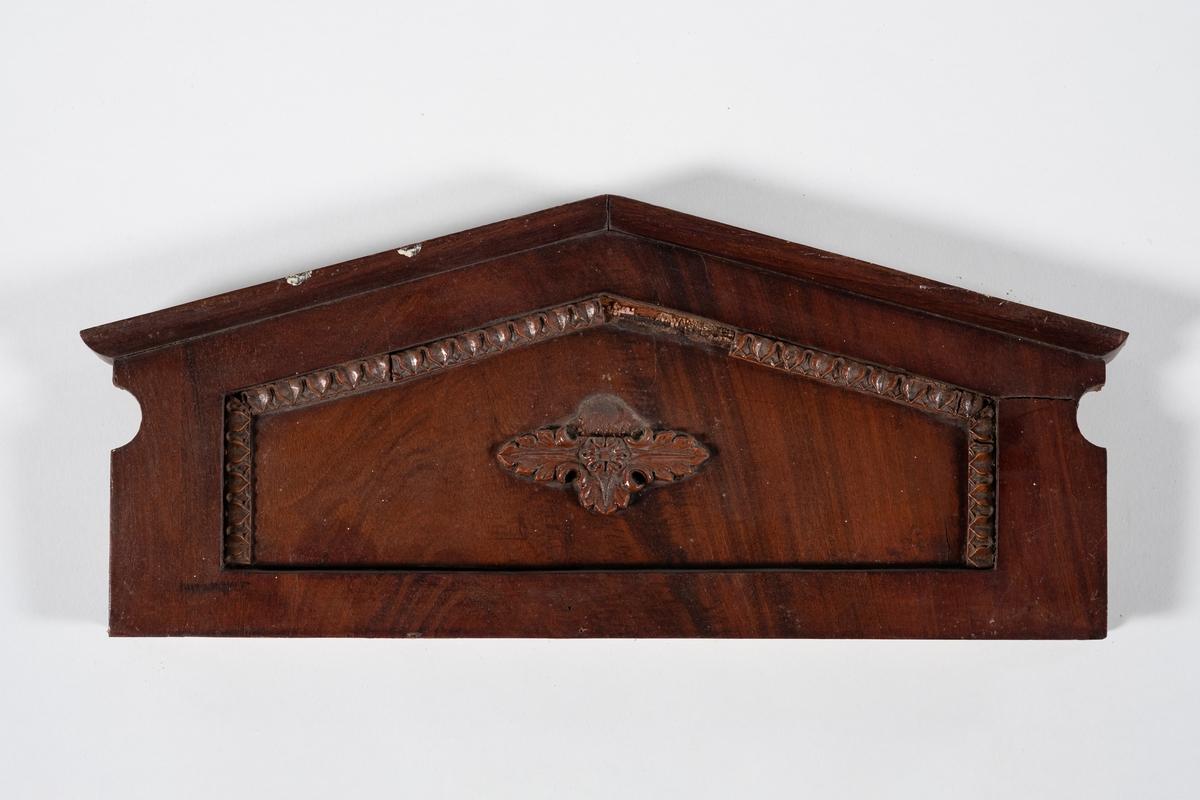 Kronlist til sengekrone med skrånet kant øverst. Kronlisten består av to planker limt sammen hvorav den ene er skåret ut. En halvsirkel er skåret inn i hver kortside. Den har utskåret bladbord og bladornament som er limt på.