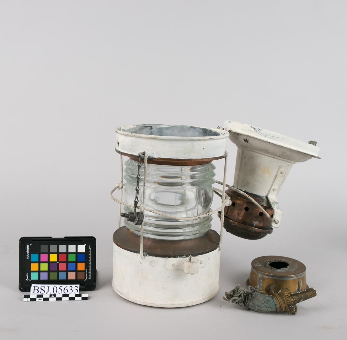 Ankerlanterne  med parafinbrenner. Rund lanterne med  hank for opphenging og åpning på topp for å komme til brenneren. Klart lampeglass med profiler.
