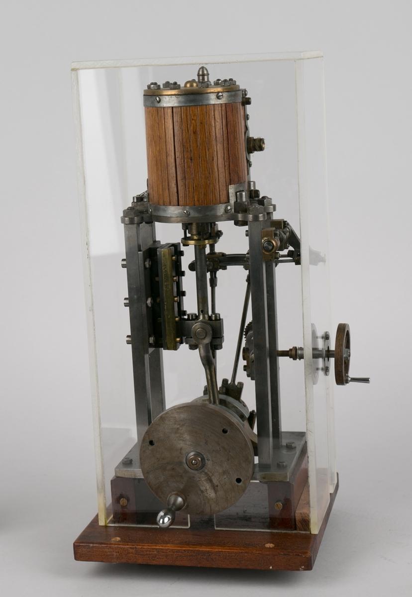 Dampmaskinmodel, en-sylindret i tre og metall med dreiehjul montert på to side. Montert i plexiglassklokke.