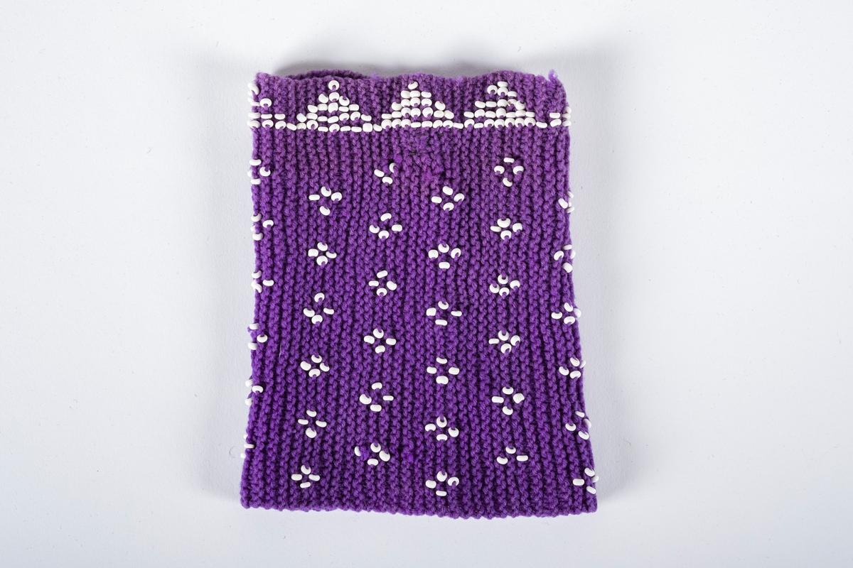 En lilla pulsvarmer som er strikket og perlebrodert.