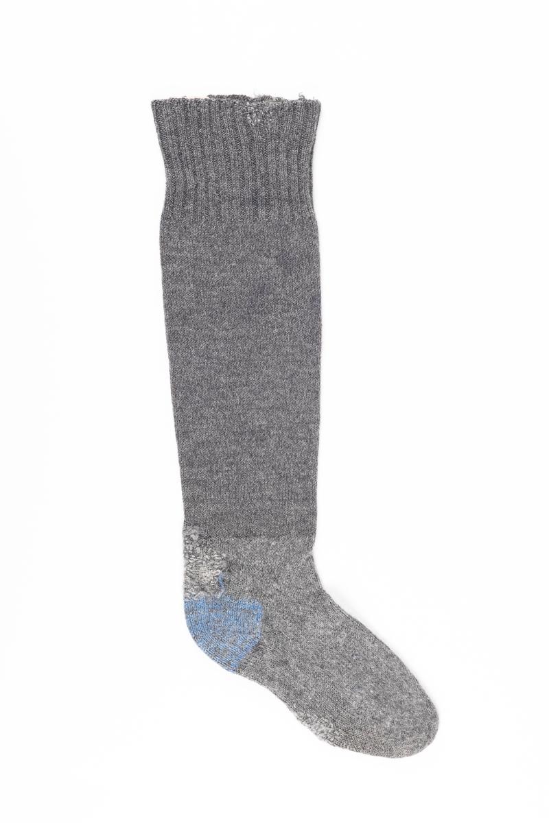 Knestrømpe strikket med grått ullgarn. Hælen er strikket med blått garn. På innsiden ved åpningen er det påsydd en lapp med fangenummer.