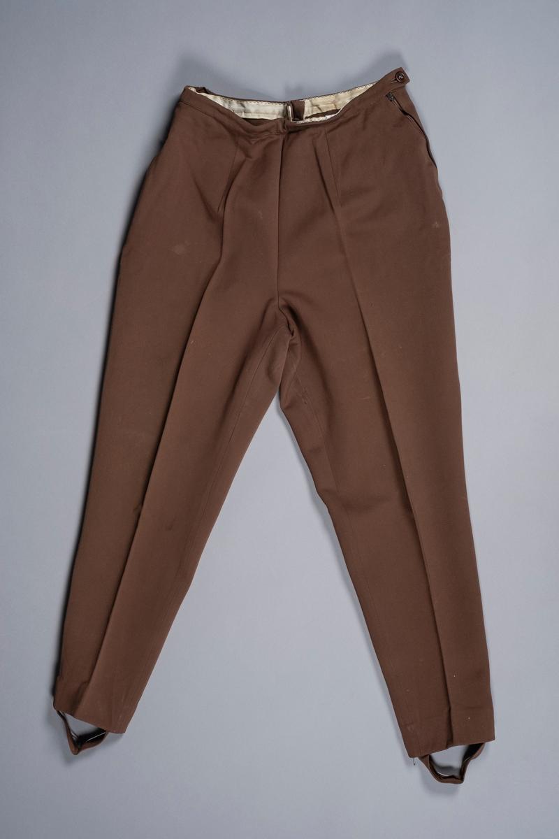 Bukse i brunt stoff som smalner nedover og ender med fotløkker. Buksen lukkes med glidelås i siden. På den andre siden er det en glidelåslomme.