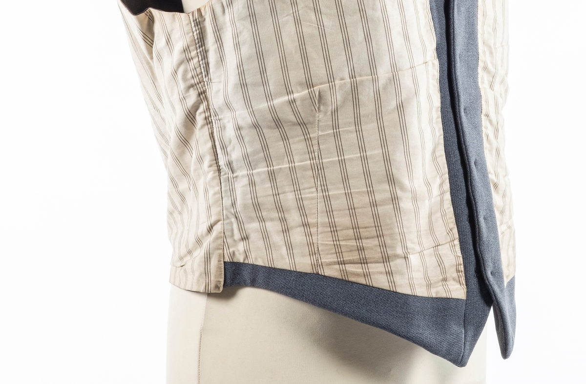 Vest med forstykke i grå ullstoff i front og bakstykke i brun sateng. Den har foring i stripete bomullsstoff. Den lukkes i front med seks knapper og har spensel i ryggen. Vesten har fire forlommer.