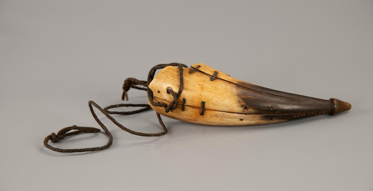 Buet horn som er gult i øvre del, mørkt i nedre. Hornet ender i en knopp. Sprekker midt bak og på sidene, sydd over med metalltråd. Innsiden er tresidet og med  innskårne initialer Å W K 1871.