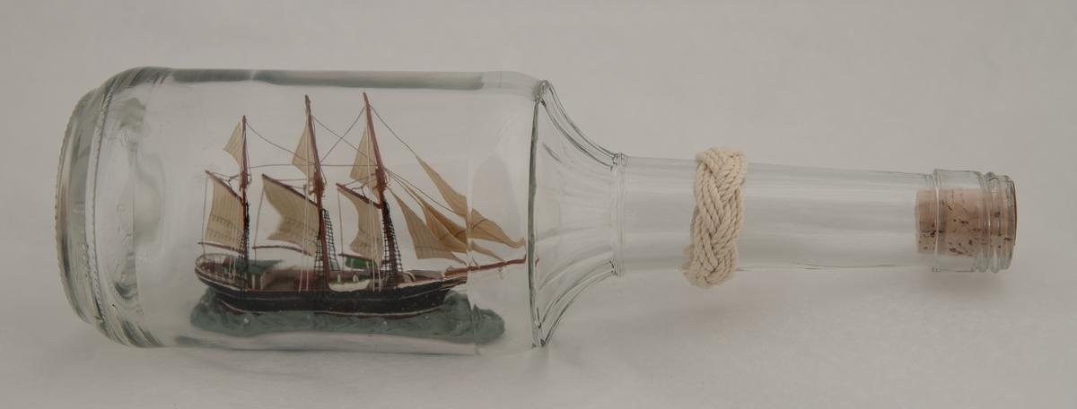 Flaskeskute: Svanen, en skonnert.  Glasset i flasken er klar.  Lys  kork.  Sortmalt skrog, det innvendige av livbåtene er grønne. På lys blå sjø. Riflete skuldre, lang hals.