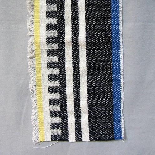 """Ett stadigt vävprov på överkast i inslagsförstärktkypert med olika inslagsfärger, svart, gul och blå. Det är tvärrandigt med 70 mm höga staplar. Varpen är av tvåtrådigt bomullsgarn. Inslaget är av halvblekt entrådigt lingarn och färgat, ullgarn, möbeltygsgarn 6/1.  Vävprov med modellnamn Randhild är formgivet av Ann-Mari Nilsson och tillverkat av Länshemslöjden Skaraborg. Det finns med  på sidan 70-71 i vävboken """"Inredningsvävar"""" av Ann-Mari Nilsson i samarbete med Länshemslöjden Skaraborg från 1987, ICA Bokförlag. Se även inv.nr. 0001-0029-0040."""