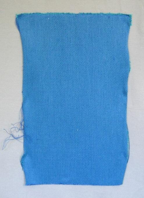 Vävprov, möbeltygprov. Ett kraftigt och stelt möbeltyg vävt i kypert med inslagseffekt. Tyget är mönstrat med 20x20 mm stora kvadrater i varpeffekt glest utspridda. (Vävprovet har ingen kvadrat.) Varpen är av tunt tvåtrådigt bomullsgarn i starkt blågrönt. Inslaget är blått entrådigt lingarn tre trådar tillsammans.  Vävprov, möbeltygsprov, med modellnamn Kvadrat är formgivet av Ann-Mari Nilsson och tillverkat av Länshemslöjden Skaraborg. Se även inv.nr. 0121 Möbelöverdrag och 0122 Vävprov samt 0123:1-3 Kudde.