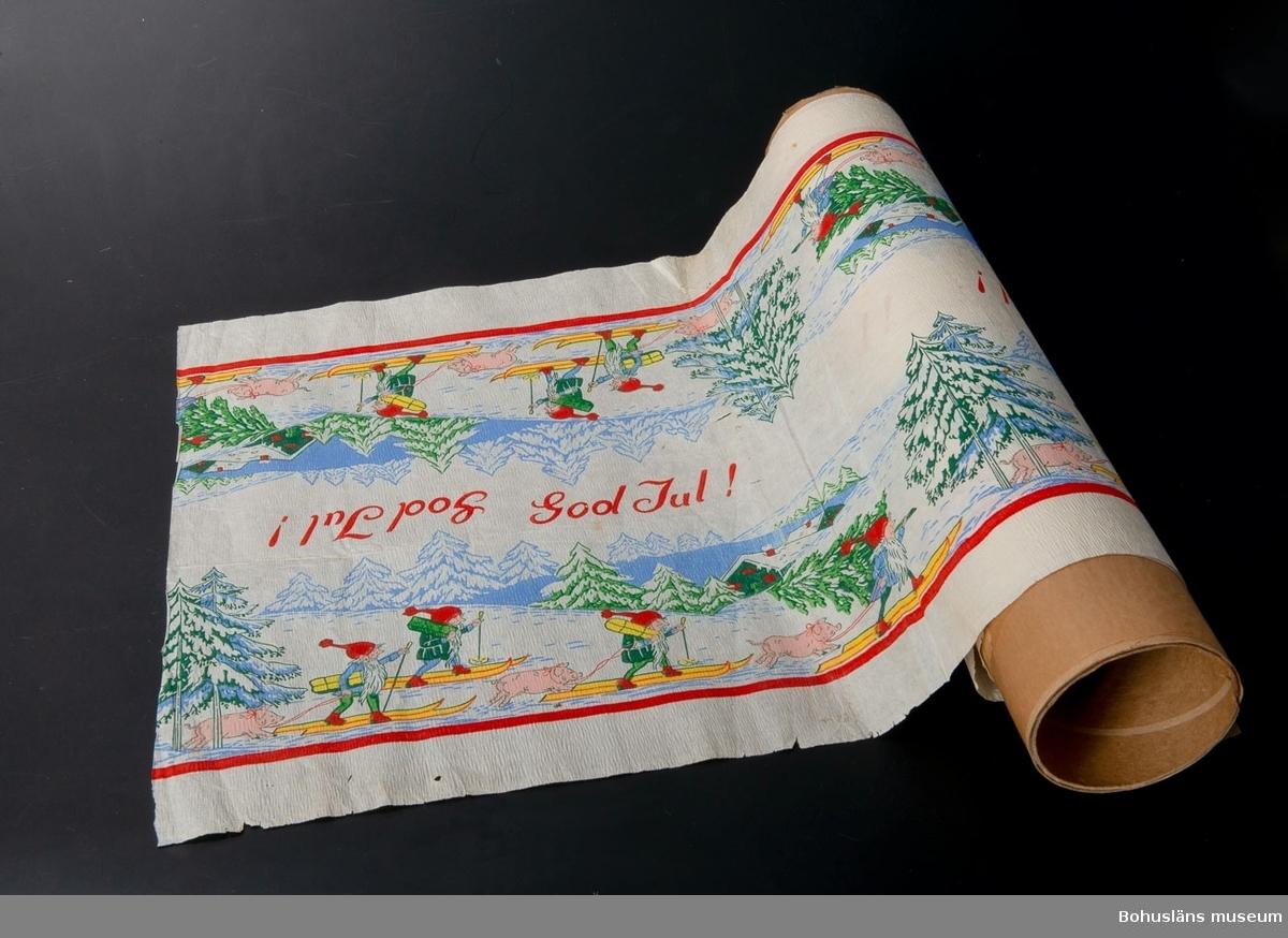 """Julmotiv: tomtar som går på skidor i ett vinterlandskap och  bär på paket och granar, en gris hålls i ledband.  Färger: Vit botten och motiv i rött, blått, grönt, gult och rosa.  Duken är en s.k. festremsa eller löpare som skall ligga i mitten av bordet och motivet finns vänt åt båda håll.  I dukens mitt finns texten: """"God Jul"""" även den är vänd så man kan läsa den åt bägge håll. Kortsidorna är avklippta och den är antagligen avklippt från en pappersrulle med duk för engångsbruk."""