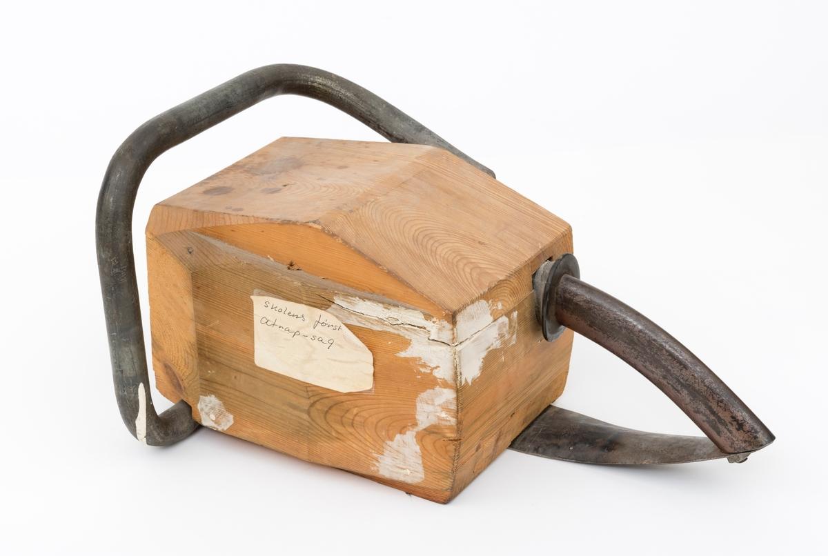 """En modell av ei motorsag, attrappsag, hovedsak utført i treverk uten sverd og sagkjede, som har vært brukt i undervisningen av elever ved Sønsterud skogskole. (Antakelig bruk til opplæring i kvisteteknikk.) Hele modellen er utformet slik at den i form og størrelse skal skal ligne på ei virkelig motorsag.  Modellens motorkropp er satt sammen av fem tilpassede trebord. Modellen er åpen i framkant. På høyre side er det to bolter med mutter som skal illustrere motorsagas sverdfeste. Den fremre håndtaksbøylen av stålrør omslutter sagkroppen. Bøylen er på undersiden av modellen skrudd fast med to treskruer. Den er videre festet med en treskrue på yttersiden av modellen, høyre side oppe. Bakre håndtak av stålrør er utformet som et pistolgrep. Bøylen er tredd gjennom en oval åpning bakkant av modellen. Det er påtredd en svart gummimansjett på bøylen som tetter åpningen i """"sagkroppen"""". På innsiden av modellen er håndtaket festet med en smidd jernkrok. Bøylen/håndtaket er videre skrudd fast til en metallplate (ser ut til å stamme fra et Sandvik-redskap, muligens buesag). Metallplata er festet på undersiden av modellen med to treskruer."""