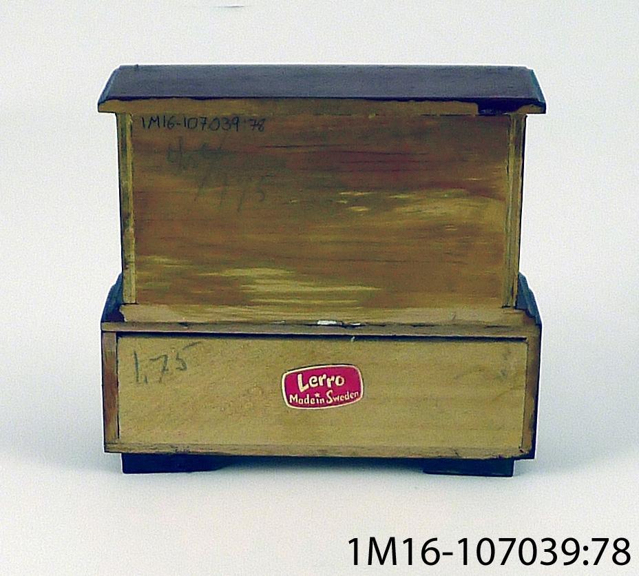 """Skåp för förvaring av porslin och linne. Ett överskåp och ett underskåp sitter ihop. Överskåpet är något mindre än underskåpet. Målat, brunt med svarta kantlister. Dörrarna på överskåpet har ett tryckt mönster i svart. Dörrarna på både över och underskåpet är öppningsbara. På hyllorna ligger rött hyllpapper och kanterna är dekorerade med blå och vita hyllremsor i papper.  Etikett på baksidan: """"Lerro Made in Sweden"""". Originalmöbelns utseende har ändrats."""