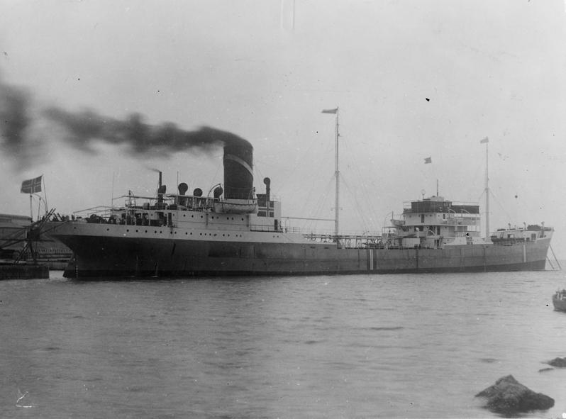 MT SVEVE (bygget i 1930) til kais. Norsk flagg i akter og norsk flagg malt på skipssiden midskips og i baug.