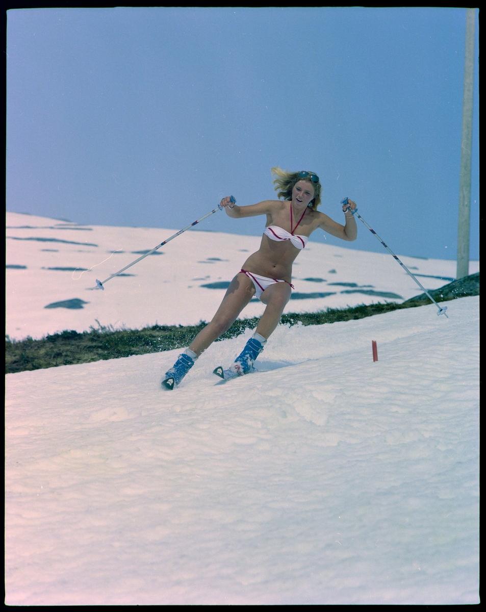 En ung kvinne står på slalom i bikini.
