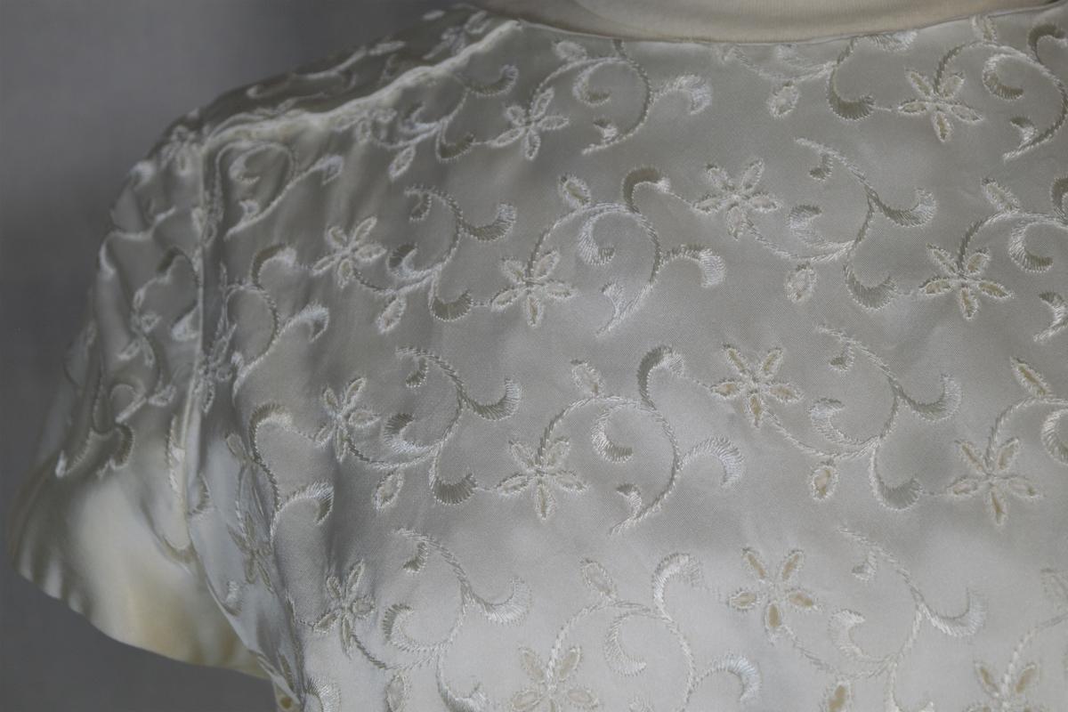 Fotsid brudekjole med lite avrundet slep (ca. 15 cm på det lengste). Brodert blomsterdekor over hele kjolen med unntak av et parti fra livet bak - slepet og sløyfen. Korte ermer. Rund hals. Fasongsydd kjole med innsnitt foran som slippes fra livet og ned. Dekorativ knepping i ryggen som ender i en sløyfe i livet bak. Slepet er foret med vliselin. Engelsk broderi (med huller).