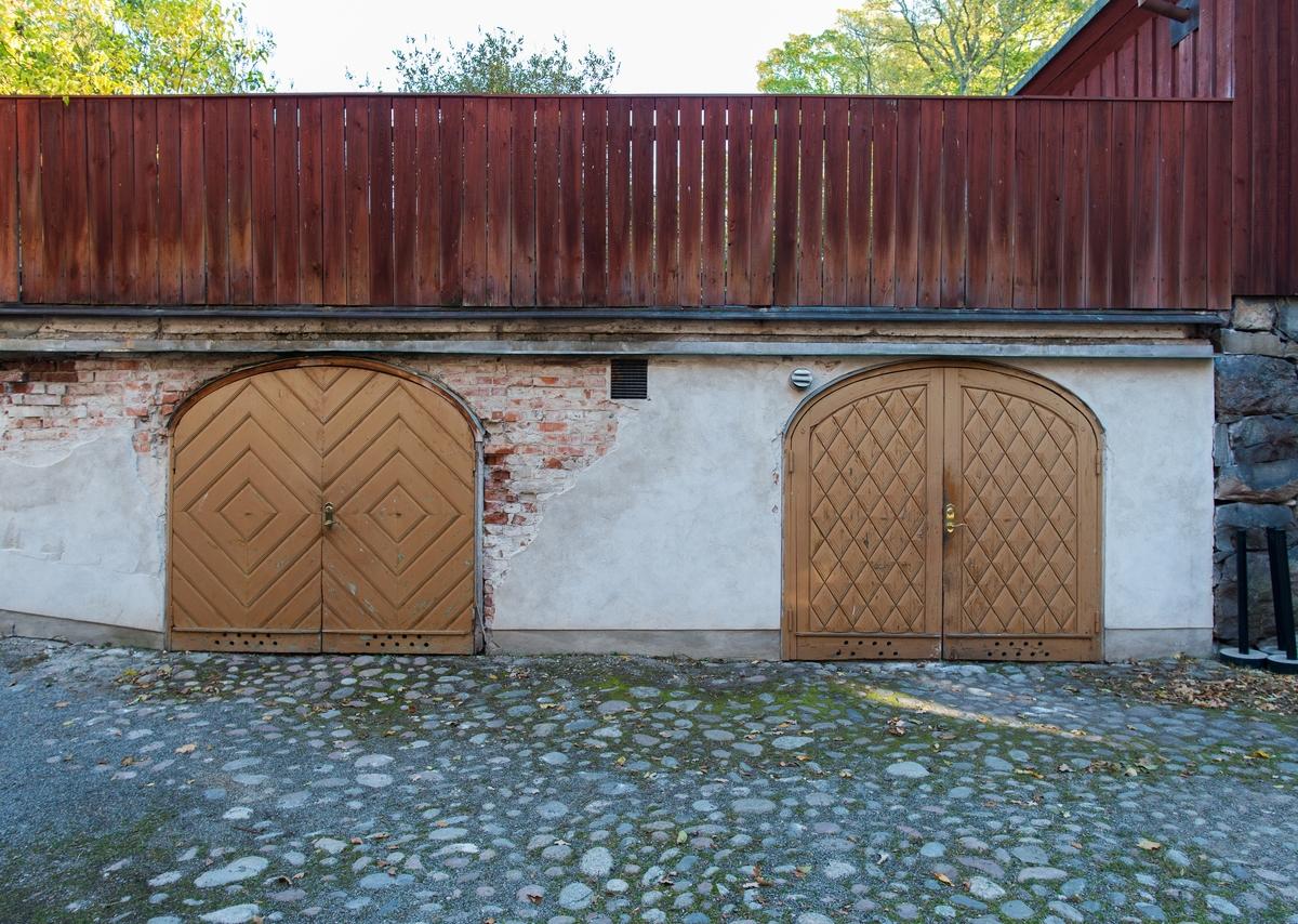 Garaget under Petissans gård är en putsad tegelmurad byggnad med betongpelare. Fasaden är vit och domineras av två rundbågiga portar med gula dörrar av trä. Byggnadens tak består av Petissans gård med uteservering.