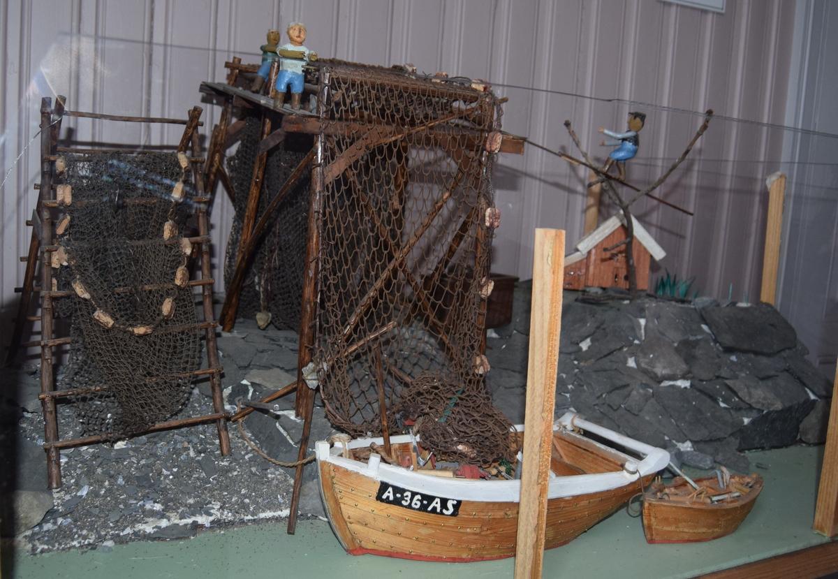 Modell av fiskejakt med registreringsnummer A-36-AS, gavlbåt (notbåt) og snekke som ligger til land hvor det forgår barking og tørking av fiskegarn. Bækvolds produksjonsnummer 33. Båten ble bygget i Hardanger i 1938 og samme år kjøpt av Ole Elias Bækvold