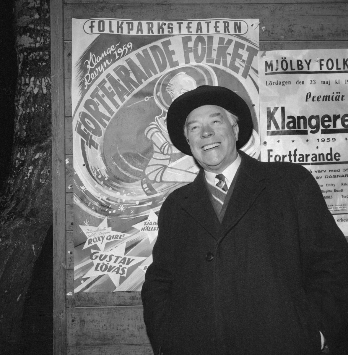 """För många lite till åren komna svenskar är Klangerevyn ett begrepp. Under åren 1935 till 1963 turnerade teaterchefen Ragnar Klange årligen med skiftande ensembler, inte sällan inberäknat Sveriges allra största artister. I revytiteln ingick alltid ordet """"Folket"""". 1959 års turne hade titeln """"Fortfarande folket"""" och premiären hölls i Mjölby folkpark den 23 maj. Bilden visar den glada teaterchefen framför parkens affischering."""