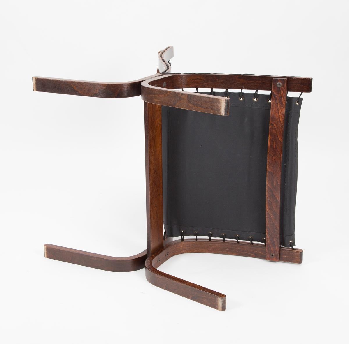 Mørk lav skinnstol uten armlener, 4 stk. Rektangulær rygg- og sittepute surret til treramme. Svært typisk 1970-tall.