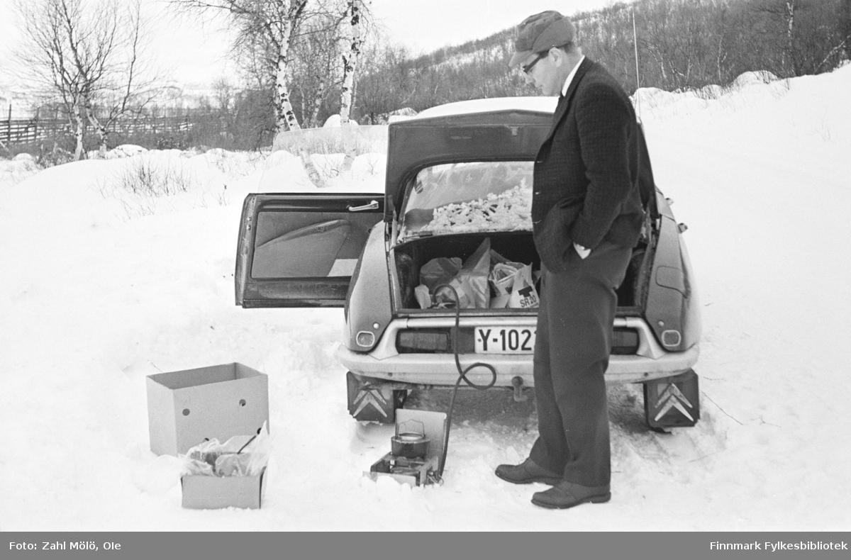 """En Citroën bil parkert lang veien. En mann koker kaffe med """"Primus"""" (tur/frilufts-kokeapparat). Hvor er bildet tatt, kanskje et sted i Tana? Tidspunkt er rundt 1970."""