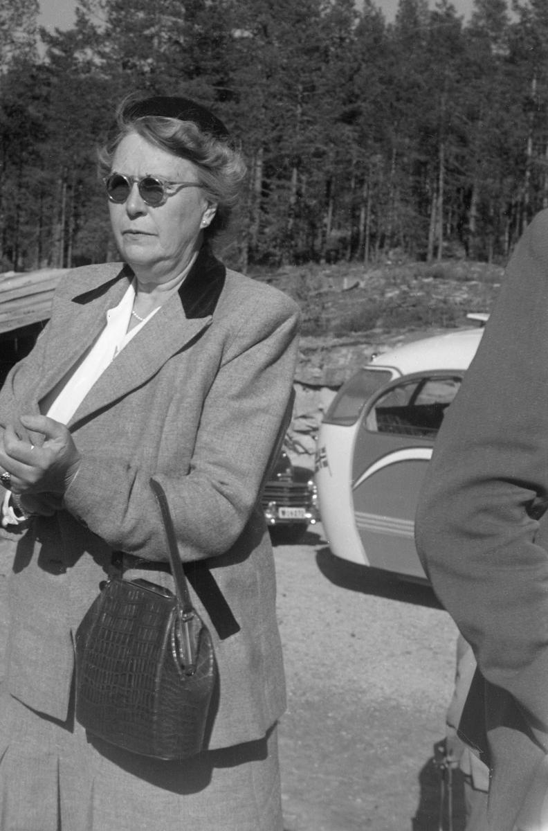 Ingeborg Bødtker (1895-1985), fotografert under Norsk fløtningsforbunds befaring i 1952. Hun var gift med [Jacob Gottfrid] Otto Bødtker (1888-1966), som først var fløtingsdirektør i Drammensvassdraget (1915-1925), deretter i Skiensvassdraget (1925-1928). Følgelig hadde hun antakelig en slags vertinnefunksjon da organisasjonen ektefellen var direktør for samlet norske fløtingsfunksjonærer og styremedlemmene i Nordisk fløtningsråd til konferanse med innlagt befaring og årsmøte høsten 1952.  Ingeborg Bødtker var kledd i ei drakt med skjørt og jakke som på fotografiet framstår som lysegrå, med unntak av den bakre delen av kragen, som er mørk. Under jakka hadde hun en kvit bluse. Ingeborg Bødtker hadde alpelue på hodet, solbriller på nesa og håndveske over venstre underarm. Ellers var hun pyntet med perlekjede og perleøredobber. I bakgrunnen ser vi bakparten på ekskursjonsbussen og fronten på en bil av merket Plymouth, antakelig en årsmodell fra perioden 1946-1948.