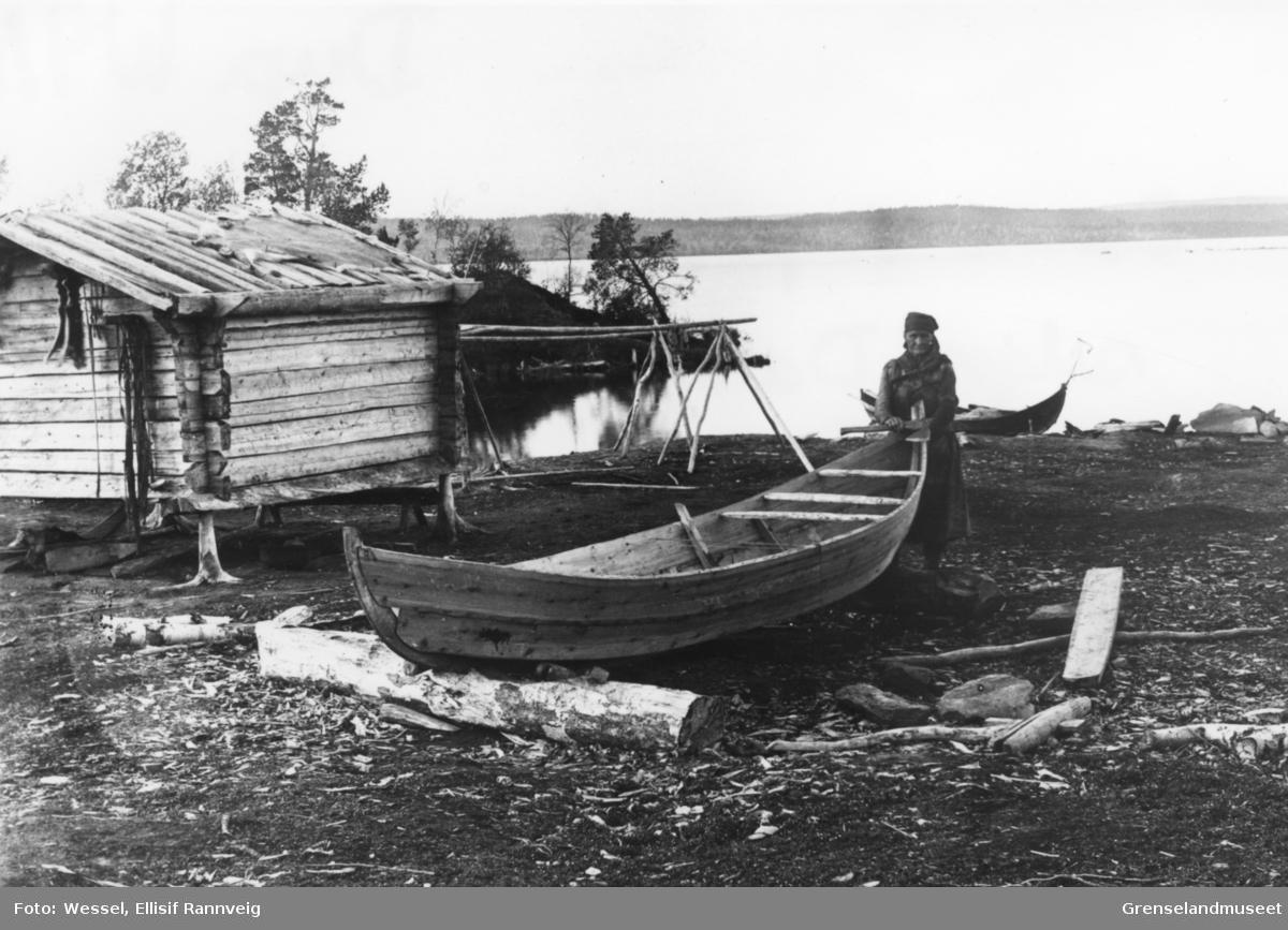 Kvinnelig båtbygger med sin nybygde skoltebask, østsiden av Borsejávri, Pasvik ca 1899. Et reinskinn ligger utspent på taket av koia.