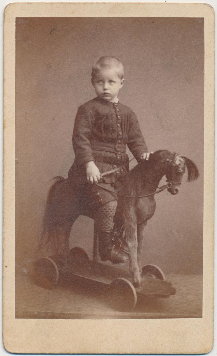 Helfigur foto av liten gutt sittende på en lekehest, ukjent