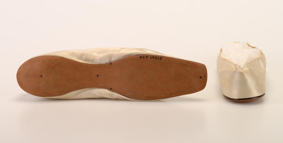 Et par damesko av hvit/elfenbensfarget silke. Foran er tåen er avrundet firkantet og ganske smal. I utringningen er det festet på en liten hvit silkesløyfe. Foran ved utringningen er det en søm på hver side av skoene. Skoene er foret med tettvevd hvit lin. Innersålen er av hvitt skinn. De har brune lærsåler på undersiden. Skoene er helt flate.