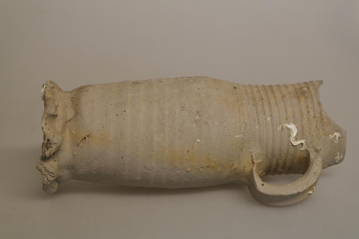 Krukke i ubehandlet keramikk. Krukken er enkelt fremstilt, med riller både på utsiden og innsiden. Det er festet ett håndtak litt på skrå øverst på krukken. I bunnen er det laget en bølgete kant.