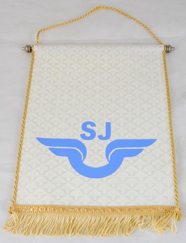 Bordsstandar med krämfärgad flagga (1). Tyget har ett upprepande mönster av SJ-loggor i gråbeige, med SJ:s logotyp tryckt i blått på mitten. Längst ned på flaggan finns fransar i guld, samt ett guldfärgat band. Långsidorna är kantade med guldfärgade snoddar. Längst upp på flaggan finns en kanal med en metallpinne.  Till flaggan finns en stång (2) av silverfärgad metall på kvadratisk fot. Högst upp på stången finns en knopp.