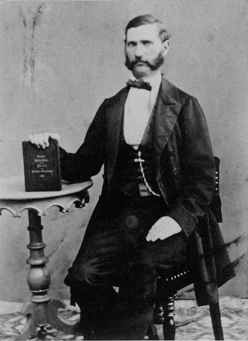 Porträtt av en man som sitter på en stol. På ett runt ombord intill håller han i en bok vars titelsida han visar - svårt att läsa titeln.